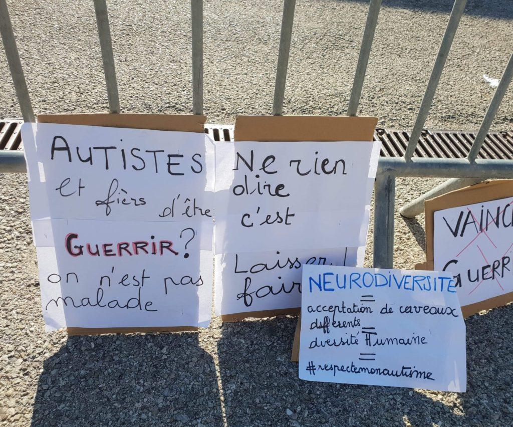 """Panneaux militants décrivant des slogans tels que """"Autistes et fiers d'être, guérir on est pas malade!"""" """"Ne rien dire c'est laisser faire"""", """"Neurodiversité= acceptation de cerveaux différents, de la diversité humaine""""."""